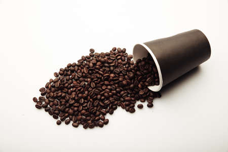Cup of coffee full of coffee beans on white background Фото со стока