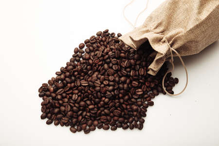Roasted coffee beans scattered of the bag isolated on white Фото со стока
