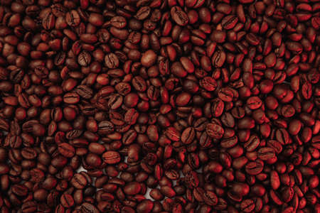 Roasted coffee beans background in red color