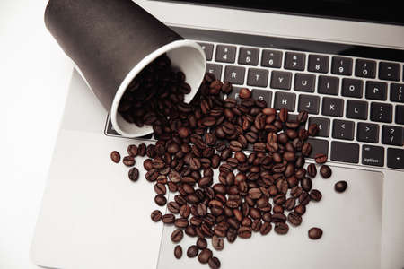 Paper cup and coffee beans on keyboard at the white desk