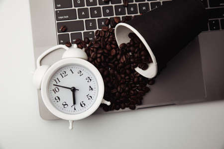 A cup of coffee on keyboard, white alarm clock and coffee beans. Morning workplace
