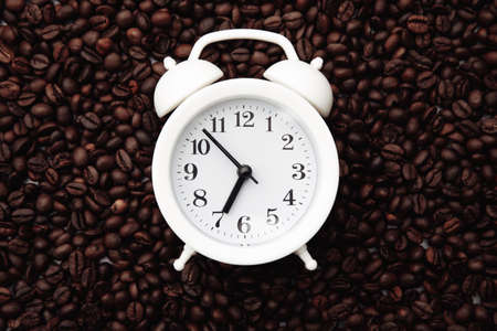 Alarm clock on coffee bean background. Morning with cup of coffee