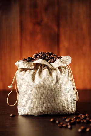 Roasted coffee beans in the bag on wooden background. Vertical image