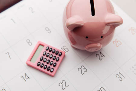 Pink piggy bank and calculator on a white calendar background, saving and investment concept. Top view