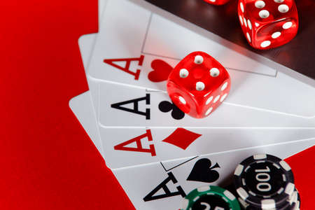 Red playing dice and cards with aces close-up