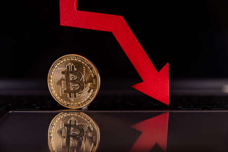 Bitcoin and red arrow down close-up. Ð¡ryptocurrency value concept