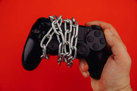 Young man holds a game controller with chain isolated on red background. Game addiction concept 版權商用圖片