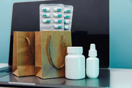 Online delivery and shopping concept. Paper bags with prescription drugs and pills and white conteiners on laptop