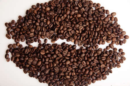 Roasted coffee beans laid out in the form of a large coffee grain close-up