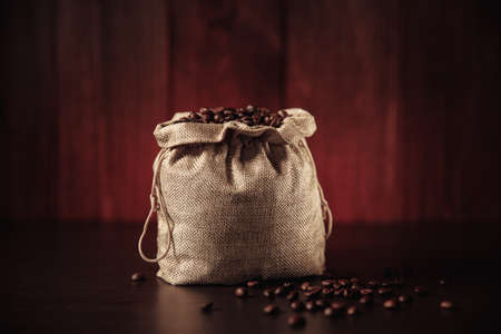 Aromatic coffee beans in bag isolated on wooden background