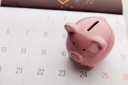 A piggy bank on a white calendar background, time to start saving