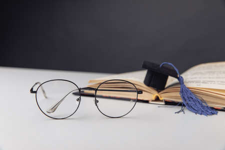 Graduation cap and glasses on a table. Education concept