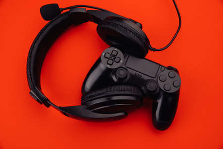 Black headphones and a gamepad on a red background. Cybersport concept