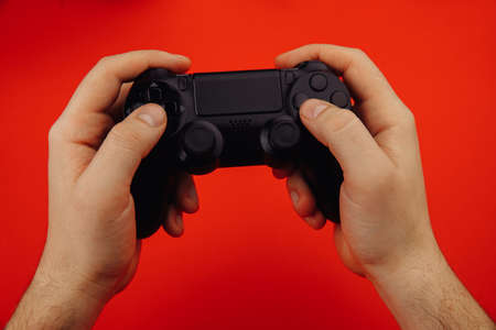 Young man holds a game controller isolated on red background