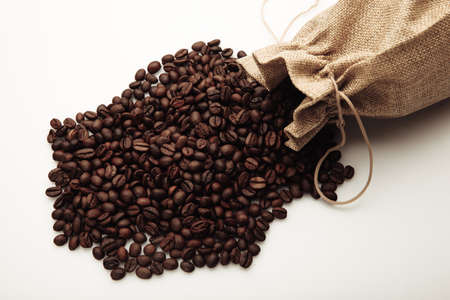 Roasted coffee beans scattered of the bag