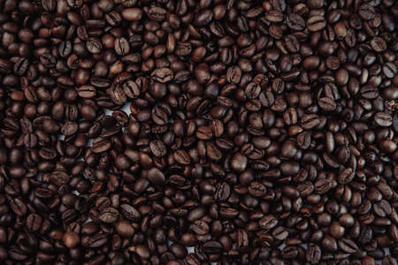 Scattered roasted coffee beans. Top view