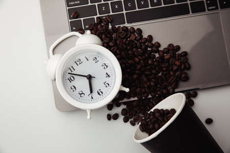 A cup of coffee on keyboard, white alarm clock and coffee beans. Morning workplace concept