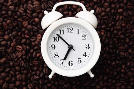 Alarm clock on coffee bean background close-up