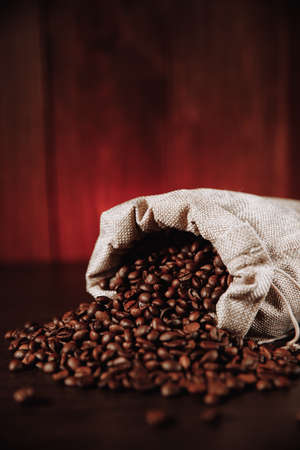 Coffee beans scattered of the bag on wooden table. Vertical image 版權商用圖片