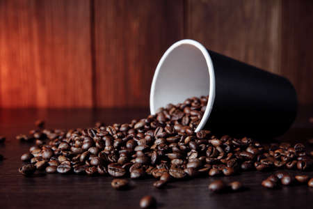 Paper cup with brown coffee beans on wooden background 版權商用圖片