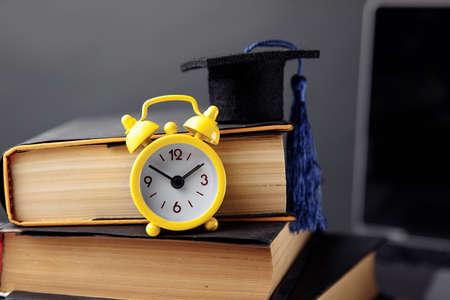 Alarm clock, graduation cap and books on table 版權商用圖片