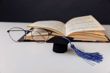 Graduation cap and glasses with open book on a table. Education concept