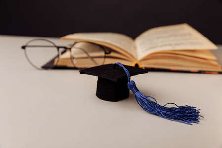 Graduation cap and glasses with open book. Education and science concept