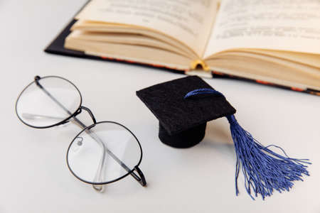Graduation cap and glasses with open book close-up. Education concept 版權商用圖片