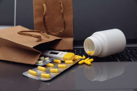 Bags with pills and drugs on a laptop keyboard. Buying medicines online theme