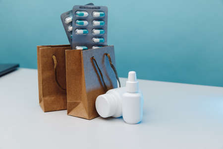 Online shopping theme. Paper bags with medical white containers and pills on blue background 版權商用圖片