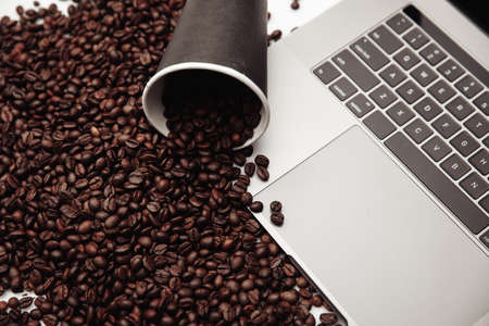 A cup of coffee on laptop and coffee beans