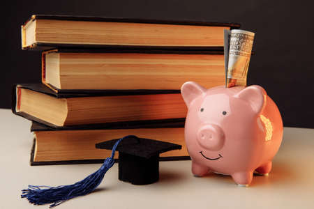 Ceramic moneybox with stack of books. College, graduate, education concept