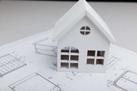 Wooden model of house on drawing close-up