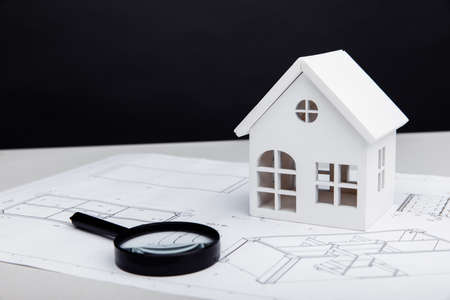 White model of house and a magnifying glass on a drawing. Real estate building concept
