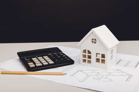 Model of house and calculator on architectural project. House building costs concept 版權商用圖片
