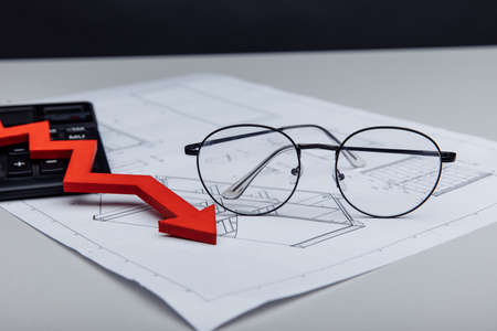 Financial and investment concept. Calculator, glasses and arrow down on architectural project 版權商用圖片