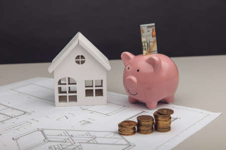 Model of house and piggy bank with dollar and coins on architectural plan. House building budget concept
