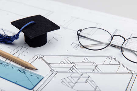 Technical drawings and graduation cap close-up. Engineering education concept