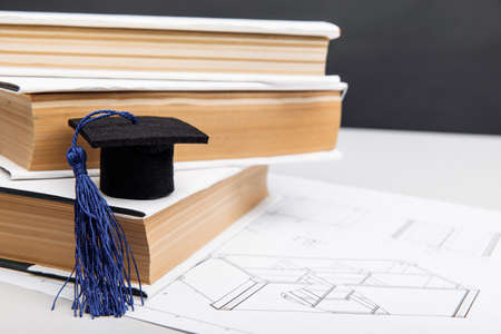 Mechanical drawings and graduation cap on books. Engineering education concept