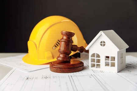 Wooden gavel, house and yellow helmet