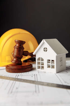 Gavel and construction plans with yellow helmet and house. Vertical image 版權商用圖片