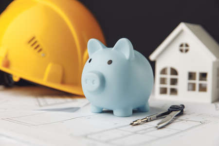 Construction safety helmet, house and blue piggy bank. Building and business concept