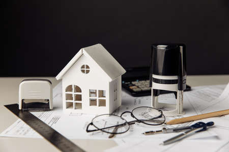 Drawing with model of house, calculator and stamps, building business and investment concept