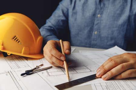Construction concept. Architect working on blueprint 版權商用圖片
