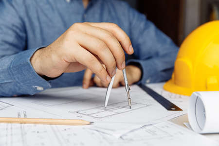 Building concept. Civil male engineer working on blueprint architectural project at desk in office