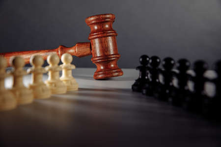 Chess pieces and law gavel on a table