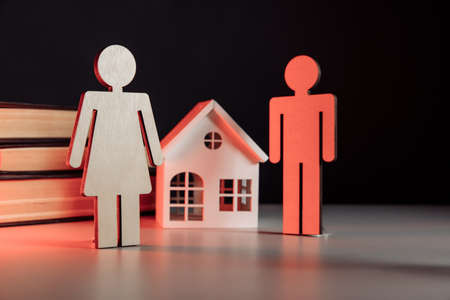 Wooden model of family and house on a table. Divorce and divide concept
