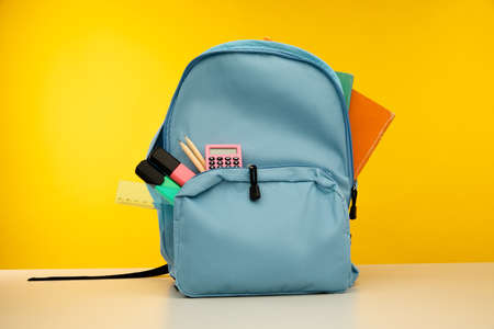 Blue backpack with different colorful stationery on table. Back to school