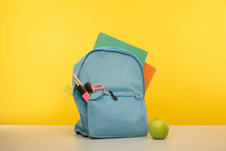 Back to school concept. Backpack with school supplies on yellow background 版權商用圖片