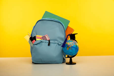 Blue backpack with school supplies with globe on yellow background 版權商用圖片